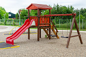 Outdoor playground with a slide and wooden swings