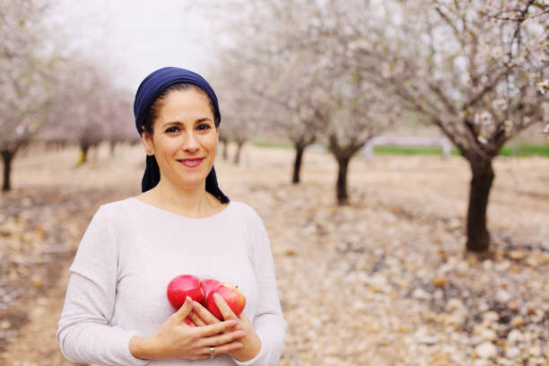 Outdoor portrait of 40 years old woman holding red apples stock photo