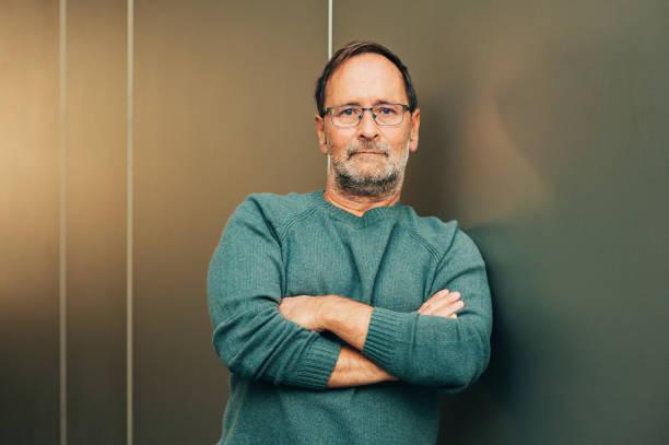 Outdoor-Porträt von 50 - 55-jähriger Mann trägt grünen Pullover und Brille, Arme gekreuzt – Foto