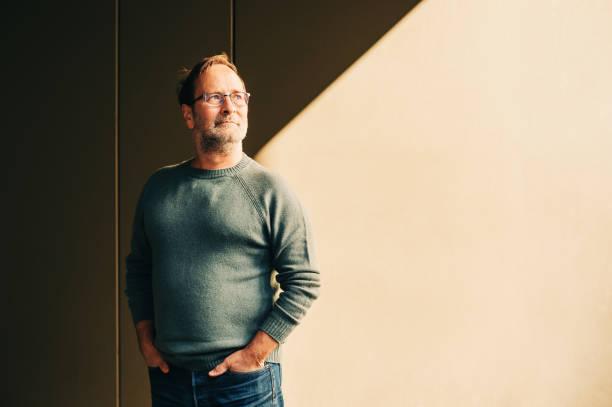 Outdoor-Porträt von 50 - 55-jähriger Mann trägt grünen Pullover und Brille, helles Schattenbild – Foto