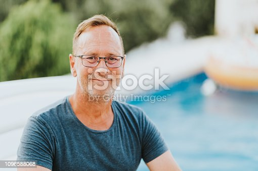 Outdoor portrait of 50 year old man resting by the pool