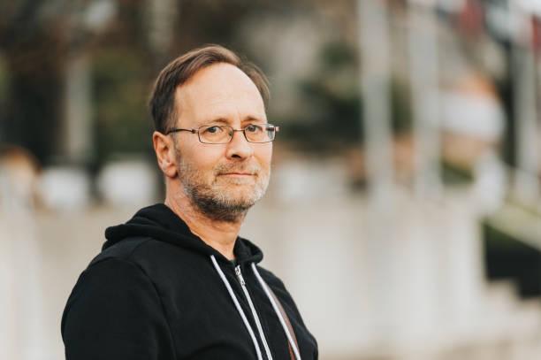 Outdoor-Porträt von 50 Jahre alten Mann mit schwarzer hoody und Brillen – Foto