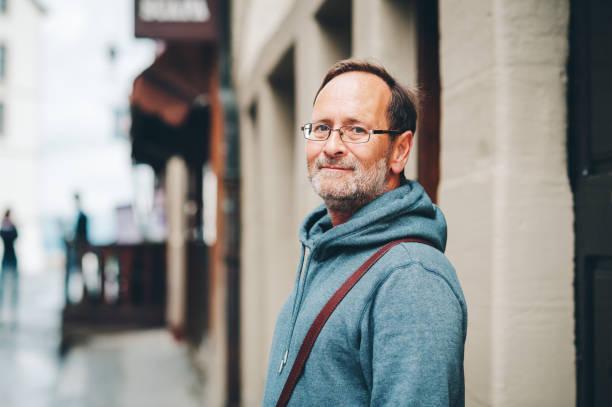 ritratto all'aperto di un uomo di 50 anni che indossa felpa con cappuccio blu e occhiali - man portrait foto e immagini stock