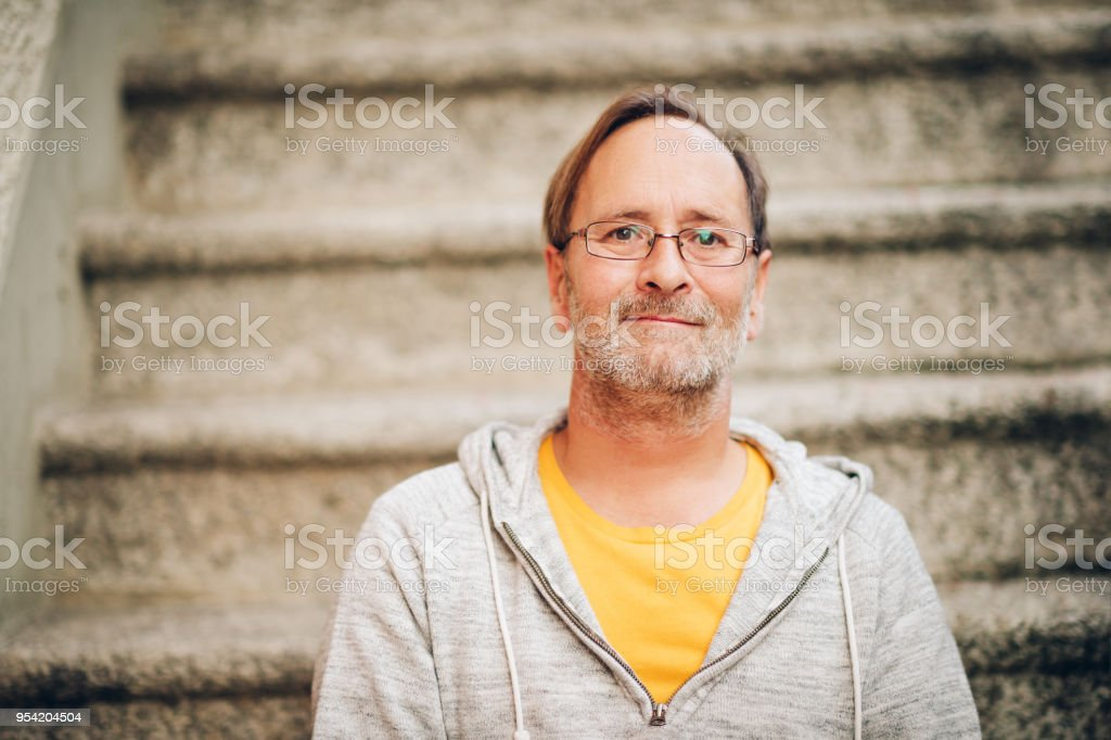 Outdoor portrait of 50 year old man wearing grey hoody and eyeglasses stock photo
