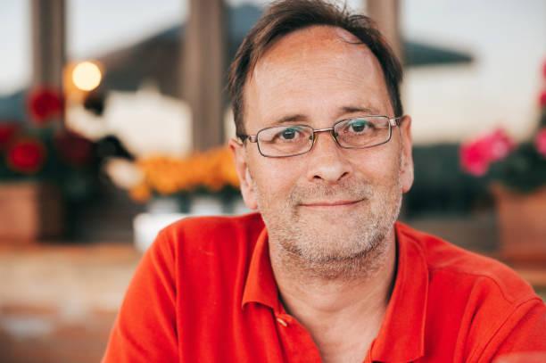 Outdoor-Porträt des 50-jährigen Mannes mit rotem Poloshirt und Brille – Foto