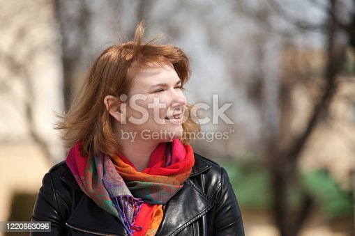 outdoor close-up portrait of a 20 year old red-haired woman in a black leather jacket