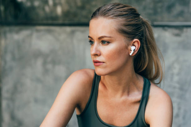 Outdoor Portrait of a Blonde Woman Runner With Wireless Earphones Outdoor portrait of a beautiful woman runner using wireless earphones. wireless headphones stock pictures, royalty-free photos & images