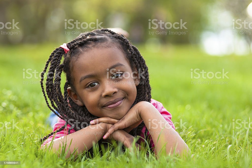Young black woman lying down on the grass — Stock Photo