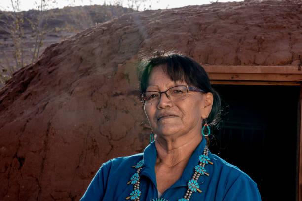 outdoor-porträt einer senior native american navajo woman vor einem traditionellen hogan im monument valley arizona - navajo stil stock-fotos und bilder