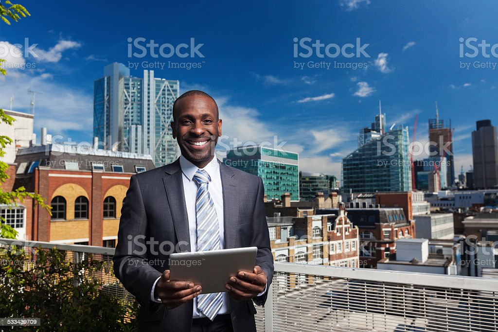 Outdoor portrait of arfo amercian businessman with digital tablet stock photo