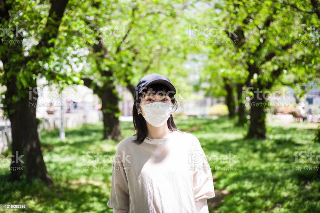 外科用マスクを着用したアジア女性の屋外肖像画 - 1人のロイヤリティフリーストックフォト