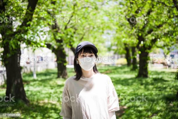 外科用マスクを着用したアジア女性の屋外肖像画 - 1人のストックフォトや画像を多数ご用意