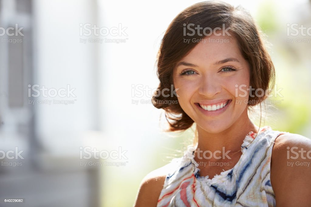 Outdoor Portrait Of Attractive Young Woman Smiling At Camera stock photo