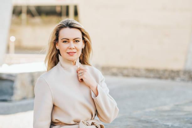 Outdoor-Porträt der schönen blonden Frau mit beigefarbenem Bausor – Foto