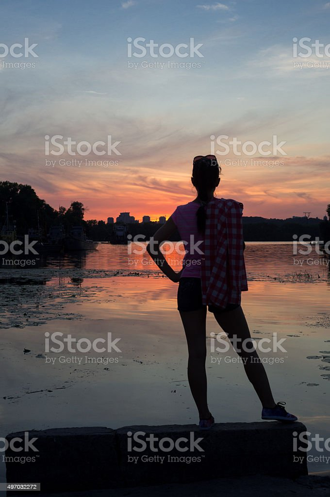 Outdoor portrait of beautiful girl at sunset on riverside stock photo
