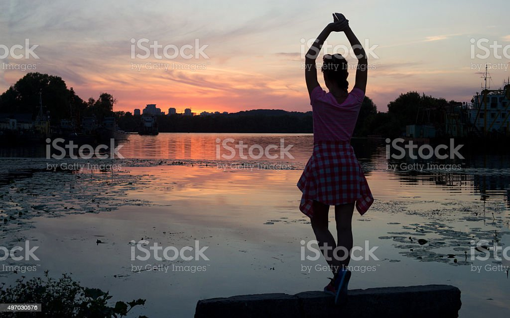 Outdoor portrait of beautiful girl at superior sunset on riverside stock photo
