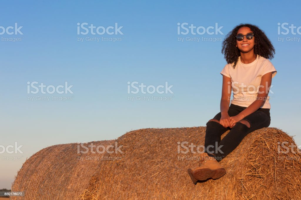 Outdoor portrait of beautiful happy mixed race African American girl teenager female young woman smiling laughing with perfect teeth and sunglasses sitting on hay bale in golden evening sunshine stock photo