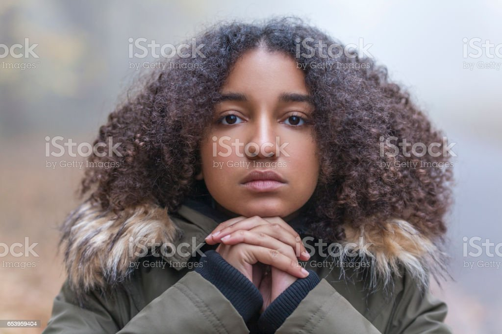 Outdoor portrait of beautiful mixed race African American girl teenager female child resting on her hands outside in a park on foggy day stock photo