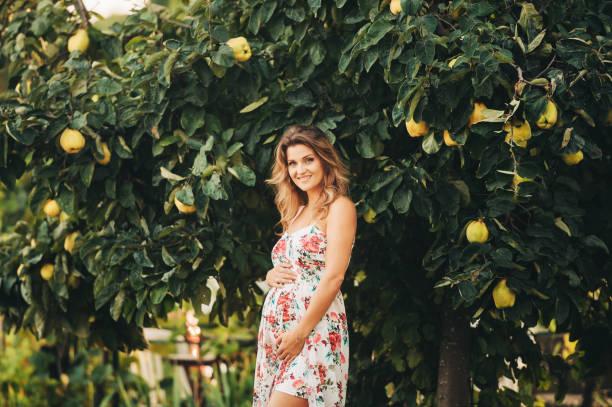 Outdoor-Porträt von schönen schwangeren Frau trägt Blumenkleid, posiert in sonnigen Garten – Foto
