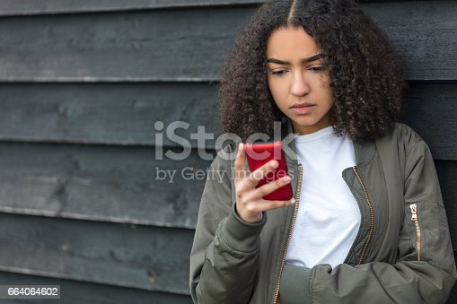 istock Outdoor portrait of beautiful sad depressed mixed race African American girl teenager female young woman texting on red cell phone wearing green bomber jacket 664064602