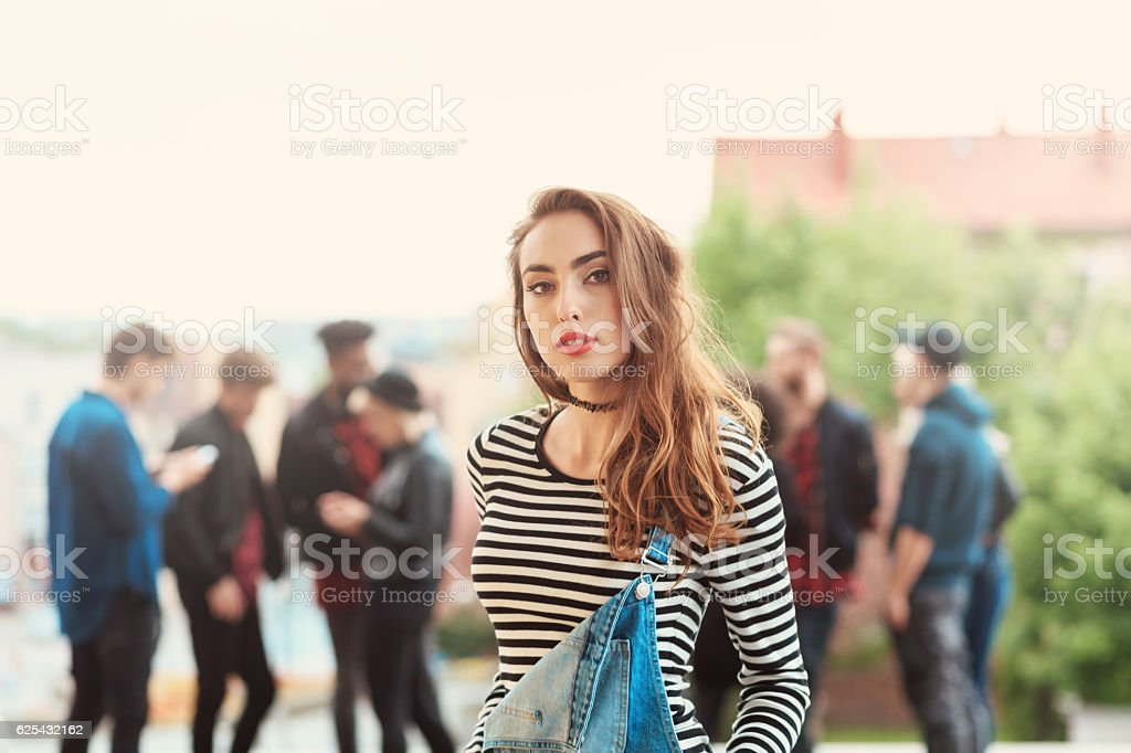 Outdoor portrait of beautiful young woman Outdoor portrait of beautiful young woman looking at camera. Multi ethnic group of people in the background. 20-29 Years Stock Photo