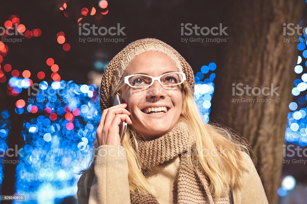 Outdoor portrait of beautiful young woman using her mobile phone stock photo