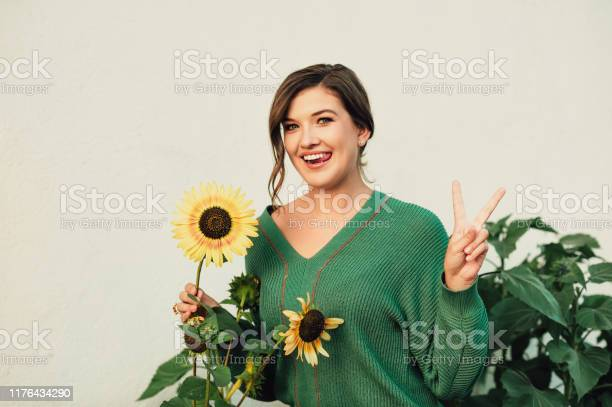 Photo of Outdoor portrait of beautiful young woman wearing warm green knitted pullover, posing with sunflower