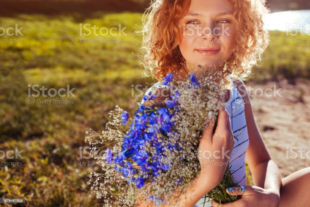 Outdoor portrait of beautiful young woman with red curly hair holding bouquet of flowers. Natural cosmetics stock photo