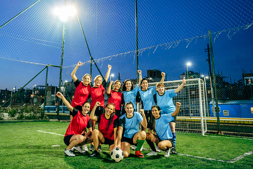 Young Hispanic footballers in 20s and 30s, wearing red and blue uniforms, standing and crouching in early evening group portrait. One teammate identifies as non-binary, the others identify as female.
