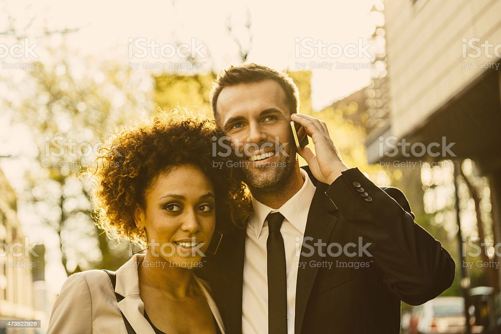 Outdoor portrait of elegant couple, man talking on phone Outdoor portrait of cheerful, elegant couple - afro amercian woman and caucasian man at sunset, man talking on smart phone. Close up of faces. 2015 Stock Photo