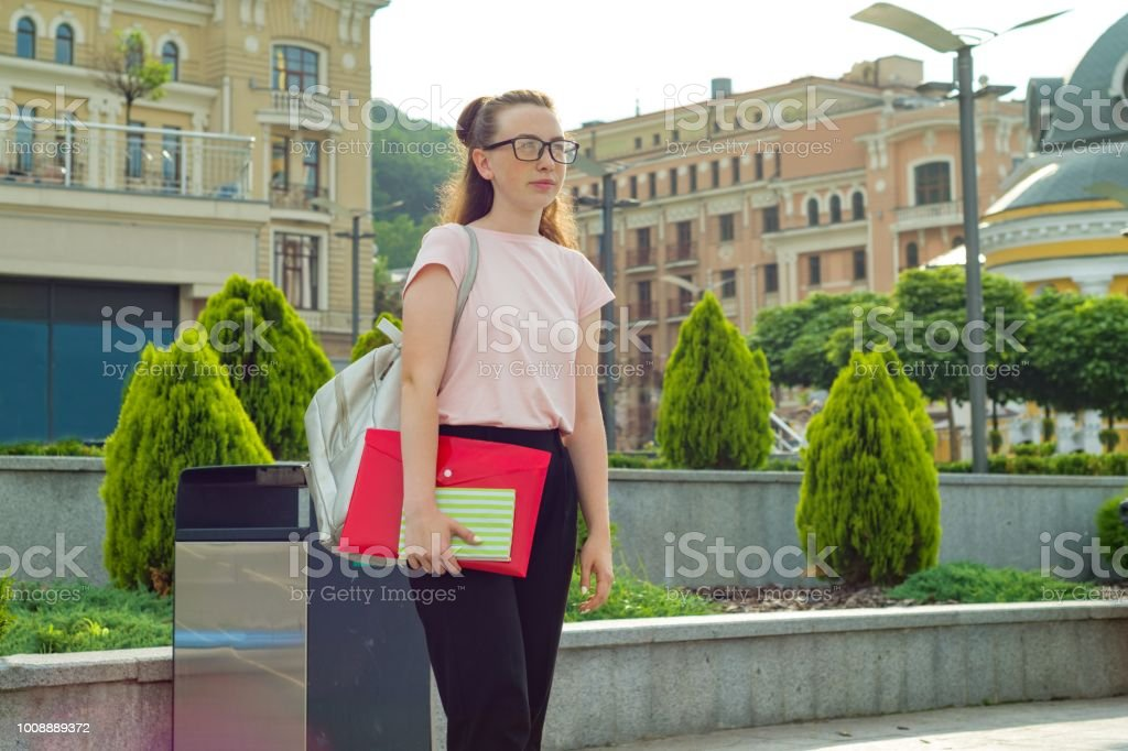 Outdoor portrait of female student 16, 17 years old. Girl in glasses, with backpack, textbooks. City background. - foto stock