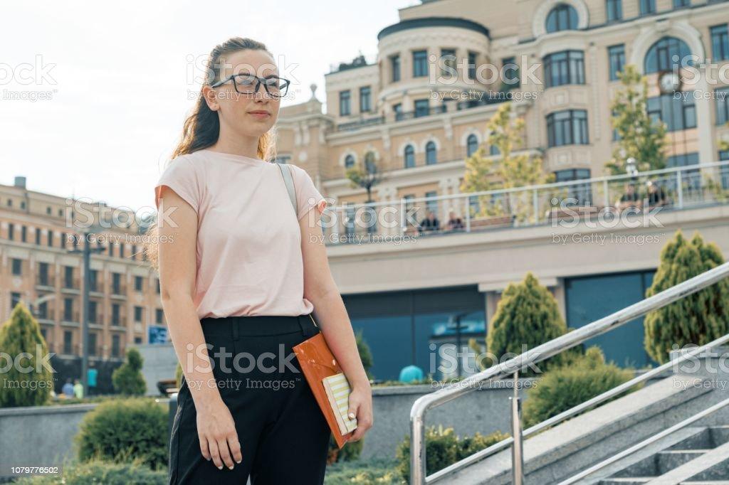 Portrait en plein air d'étudiante 16, âgé de 17 ans. Fille à lunettes, avec sac à dos, manuels scolaires. Fond de ville - Photo