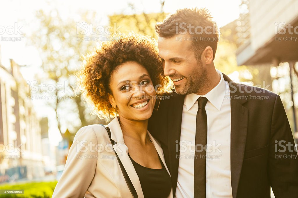 Outdoor portrait of flirting elegant couple Outdoor portrait of cheerful, elegant couple - afro amercian woman and caucasian man at sunset. Close up of faces. 2015 Stock Photo