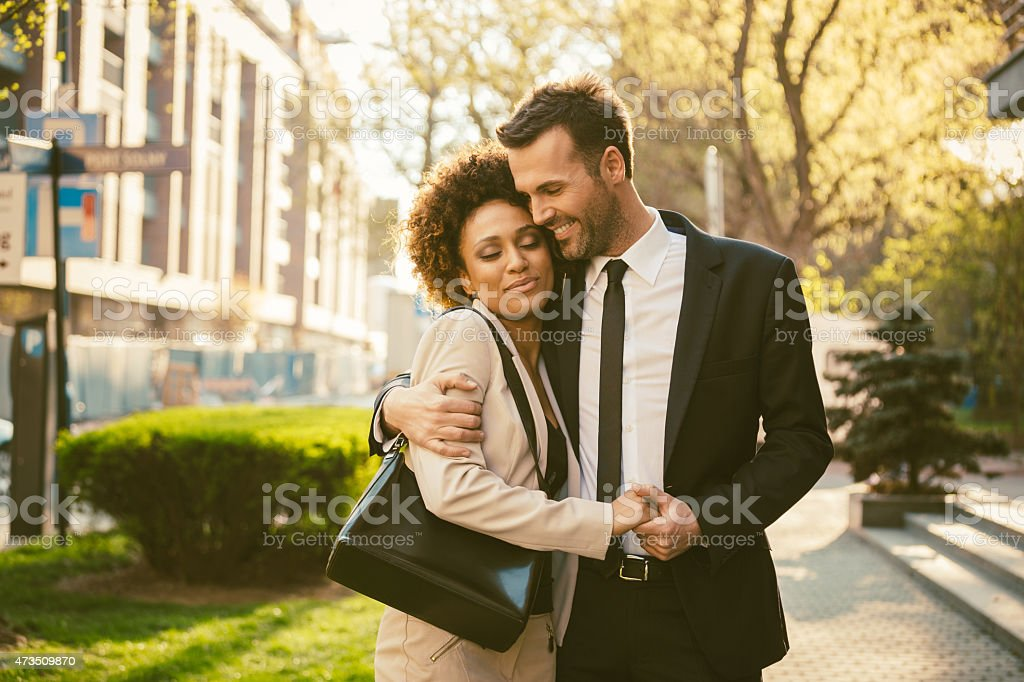 Outdoor portrait of flirting elegant couple Outdoor portrait of happy elegant couple - afro amercian woman and caucasian man, embracing at sunset.  2015 Stock Photo