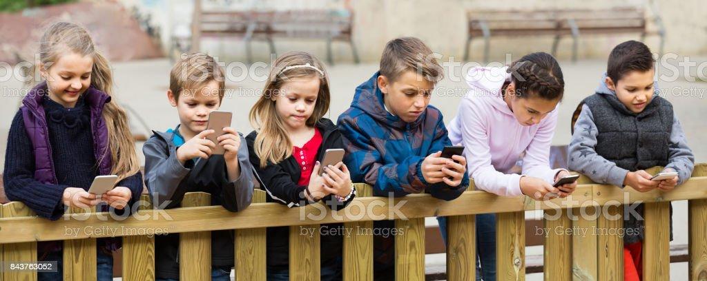 Retrato ao ar livre de meninas e meninos brincando com celulares - foto de acervo