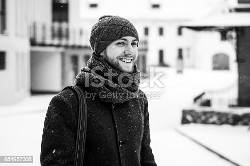 Outdoor portrait of handsome man in gray coat. Fashion photo. Beauty winter snowfall style. Black and White.