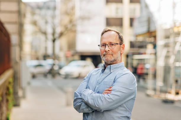 Outdoor-Porträt von hübschen Mann mittleren Alters, der lange Ärmel Oxford-Hemd trägt, posiert auf der Stadtstraße, Arme gekreuzt – Foto