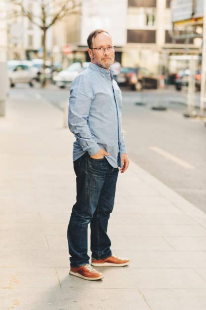 Outdoor-Porträt eines hübschen Mittelaltermanns, der lange Ärmel in Oxford Shirt trägt, posiert auf der Stadtstraße, Hand in Jeans-Tasche hält – Foto