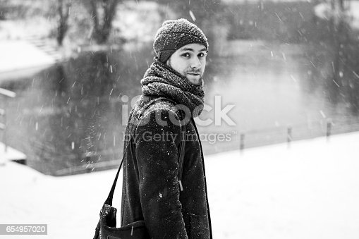 Outdoor portrait of handsome young man in snowy winter forest. Snowfall. Guy looking away on frozen river. Black and white.