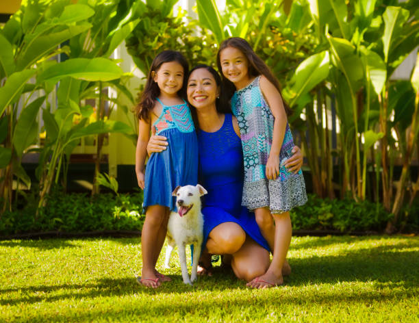 outdoor portrait of hawaiian polynesian family with mother, children and pet dog - hawaiian ethnicity stock photos and pictures