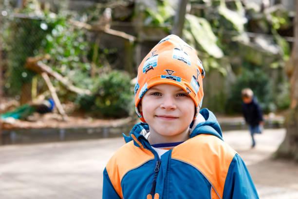 outdoor portrait junge kind im frühjahr oder herbst bunte kleidung. fröhlicher junge spaß in einem zoo. - vorschulzoothema stock-fotos und bilder