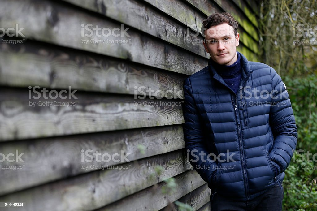 Outdoor Portrait Of Man Leaning Against Wooden Building stock photo