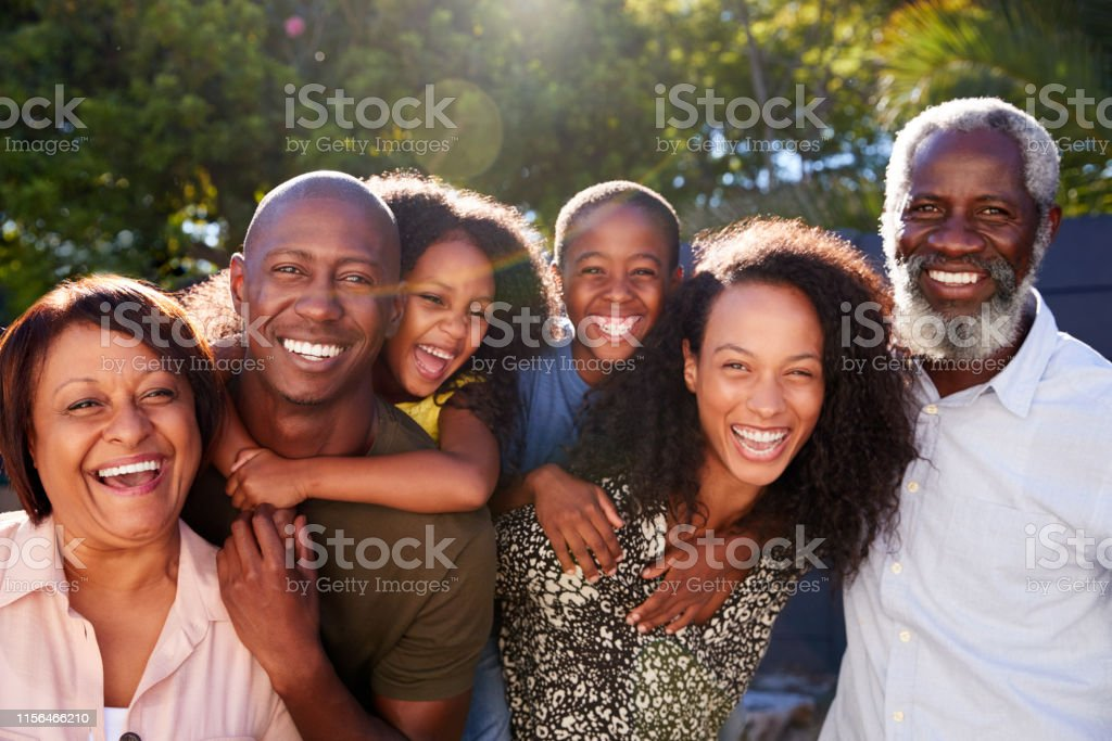 Outdoor Portrait Of Multi-Generation Family In Garden At Home Against Flaring Sun Outdoor Portrait Of Multi-Generation Family In Garden At Home Against Flaring Sun 20-29 Years Stock Photo