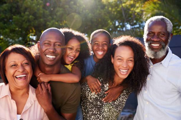 ritratto all'aperto della famiglia multi-generazione in giardino a casa contro il sole svolagliante - family foto e immagini stock