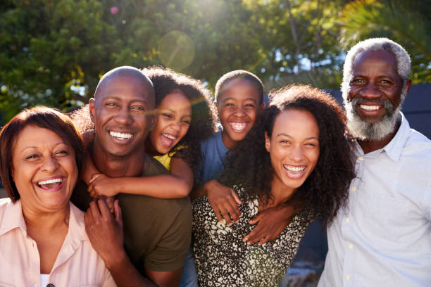 Outdoor Portrait Of Multi-Generation Family In Garden At Home Against Flaring Sun Outdoor Portrait Of Multi-Generation Family In Garden At Home Against Flaring Sun african american ethnicity stock pictures, royalty-free photos & images