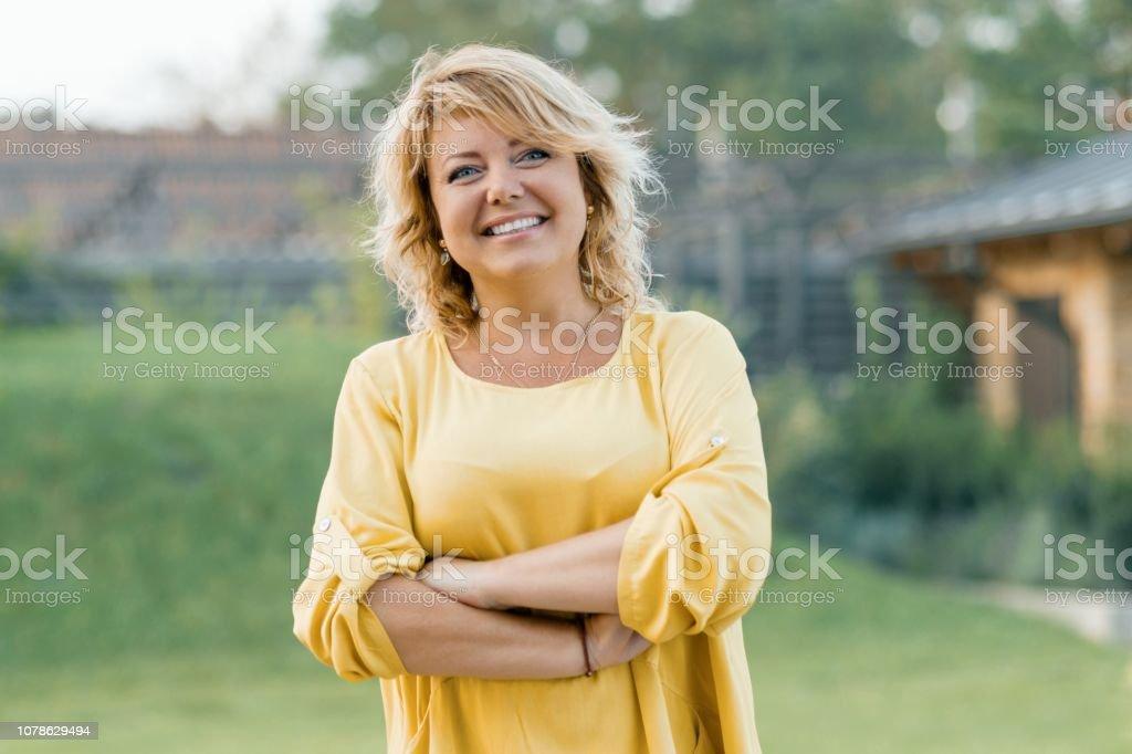Outdoor Portrait positiv selbstbewusste Reife Frau. Lächelnde weibliche Blondine in einem gelben Kleid mit Arme gekreuzt in der Nähe des Hauses - Lizenzfrei 40-44 Jahre Stock-Foto