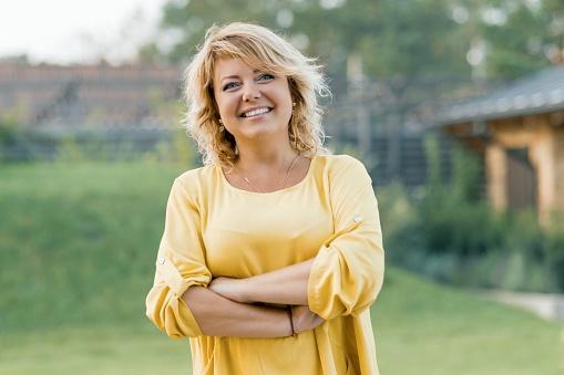 Outdoor Portrait Positiv Selbstbewusste Reife Frau Lächelnde Weibliche Blondine In Einem Gelben Kleid Mit Arme Gekreuzt In Der Nähe Des Hauses Stockfoto und mehr Bilder von 40-44 Jahre