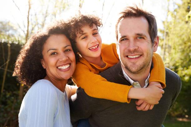 ritratto all'aperto di famiglia sorridente in giardino a casa contro il sole svolagliante - family foto e immagini stock