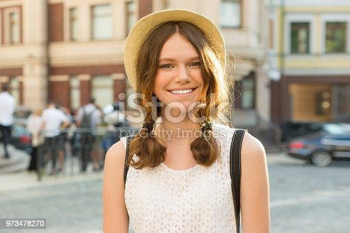 Outdoor portrait of teenage girl 13, 14 years old, city street background.