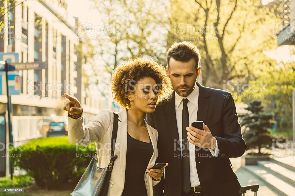 Outdoor portrait of two business people with smart phones Outdoor portrait of caucasian businessman and afro-american businesswoman using a smart phones at sunset. Woman pointing with index finger. 2015 Stock Photo